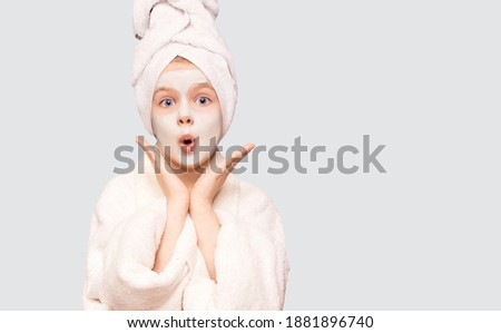 Confused unaware child girl isolated on white background spreads hands sideways, applies facial mask for looking beautiful, dressed in white robe and towel on head, hesitates about something Royalty-Free Stock Photo #1881896740
