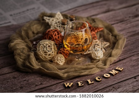 "Warm and cozy still-life picture with soft fabric, cognac\brandy glass, some new year\christmas decoration and ""Welcome"" title made of wooden letters. Vintage newspaper and plank table in background."