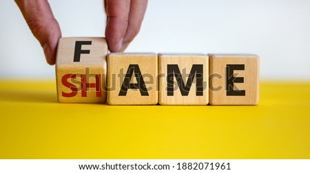 Fame or shame symbol. Male hand flips wooden cubes and changes the word 'shame' to 'fame' or vice versa. Beautiful yellow table, white background, copy space. Business and fame or shame concept. #1882071961