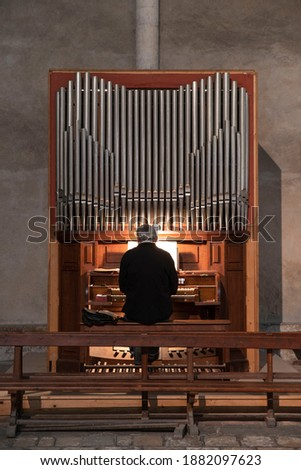 A man plays the organ in a church Royalty-Free Stock Photo #1882097623