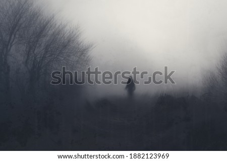 A blurred, mysterious figure with glowing eyes, standing next to a forest. With an artistic, abstract edit. Royalty-Free Stock Photo #1882123969