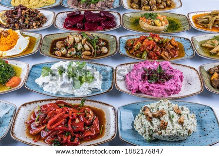 Traditional Turkish and Greek dinner meze table. Turkish Cuisine Cold Appetizers (appetizers with olive oil). Turkish appetizers in colorful plates. yogurt and various boiled herbs #1882176847