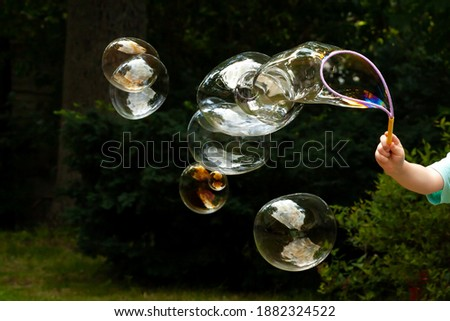 Lots of huge soap bubbles floating in the air in the garden, child blowing many big bubbles in the backyard, outside, outdoors scene. Beautiful bubbles group flying closeup, childs hand