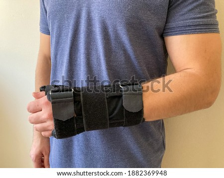 A man wearing wrist splint. Hand injury.  Sprained arm with splint. Pain in the wrist. Black wrist splint for left hand. Broken wrist and arm recovery with immobilizer. #1882369948
