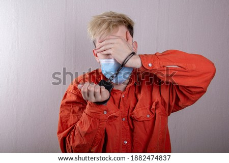 A teenager in handcuffs and a medical mask holds his head against a gray background.Headache for juvenile delinquents in quarantine, criminal liability. Members of youth criminal groups. Royalty-Free Stock Photo #1882474837