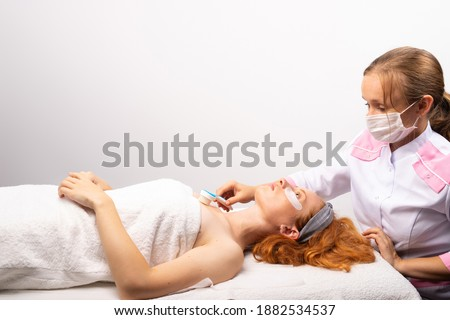A beautician wearing a medical mask and a white robe working with a massage skin brush for a red-haired girl.