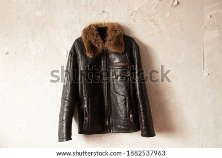 black leather winter mens jacket hanging on a hanger on the wall Royalty-Free Stock Photo #1882537963
