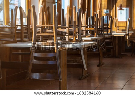 Covid 19 and closed restaurant with chairs on tables because of lockdown or shutdown. horizontal Royalty-Free Stock Photo #1882584160