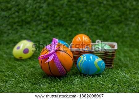 Basketball for Easter Holiday with Basketball and Easter eggs in basket on green grass