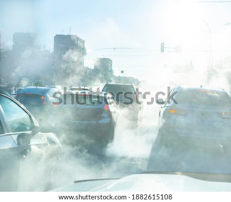 air pollution from the exhaust of cars in the city during the cold day, environmental pollution in the city Royalty-Free Stock Photo #1882615108