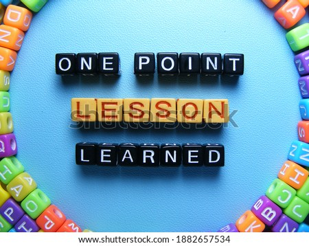 Top view of conceptual words ONE POINT LESSON LEARNED made of square letter blocks surrounded by colorful ones with fresh blue background. This terms is popular at the office and many businesses