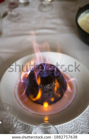 Close up on a Christmas pudding on fire on a table top. Royalty-Free Stock Photo #1882757638