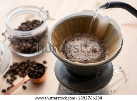 Pour hot water over the coffee powder.Make drip coffee. Royalty-Free Stock Photo #1882766284