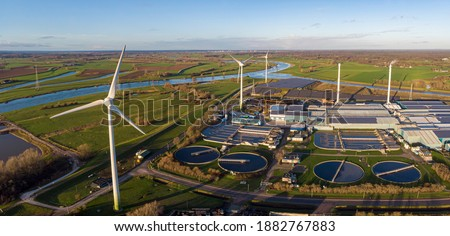 Wind turbines, water treatment and bio energy facility and solar panels in The Netherlands part of sustainable industry in Dutch flat river landscape against blue sky. Aerial circular economy concept. Royalty-Free Stock Photo #1882767883