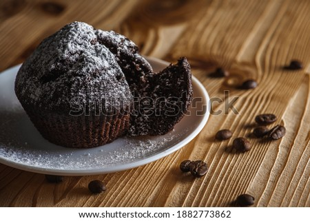 Homemade delicious chocolate muffin, pastries, buns on a white bowl on a wooden surface, close up. The concept of delicious pastries Royalty-Free Stock Photo #1882773862