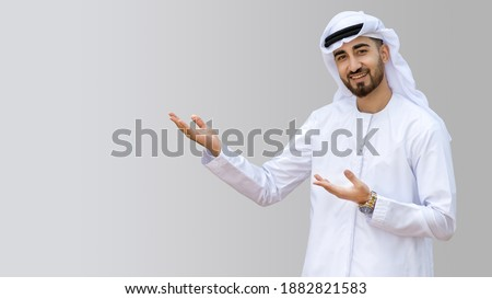 Young handsome Emirati business man in UAE traditional outfit showing a variety of hand gesture. Arabic ambitious mature businessman. Royalty-Free Stock Photo #1882821583