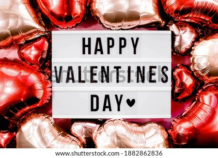 Stylish text frame lightbox with the inscription happy Valentine's day. Pink, red and beige hearts all around. Foil balloons top view of Valentine's Day. Copyspace. Royalty-Free Stock Photo #1882862836