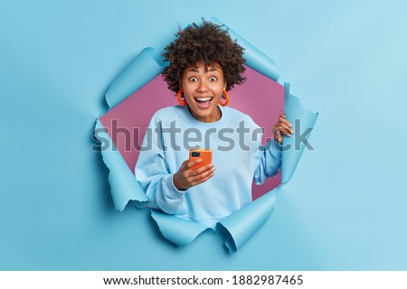 Positive curly haired woman smiles broadly uses smartphone reads funny news on website reacts on something awesome and pleasant dressed in casual jumper poses in ripped hole. Staying always in touch Royalty-Free Stock Photo #1882987465