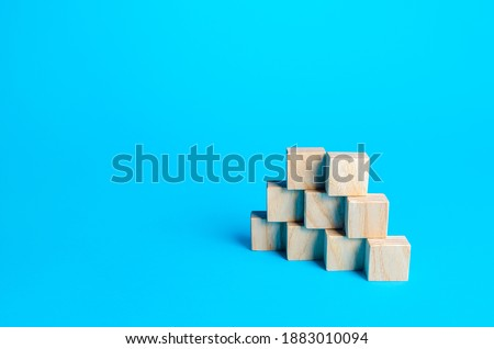 Wooden blocks pyramid on a blue background. Slide for presentation. Copy space, place for text. Steps. Minimalism. Simple shapes geometry.