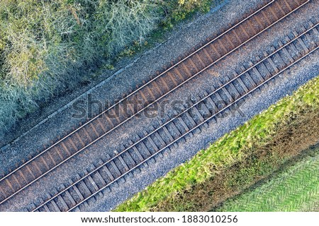 Two railway tracks which consists of two parallel steel rails, anchored perpendicular to members called ties (sleepers) of concrete to maintain a consistent distance apart, or rail gauge. With trees. Royalty-Free Stock Photo #1883010256