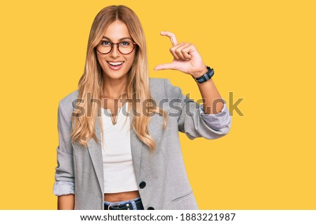 Beautiful blonde young woman wearing business clothes smiling and confident gesturing with hand doing small size sign with fingers looking and the camera. measure concept.  Royalty-Free Stock Photo #1883221987