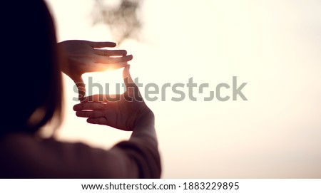 New year planning and vision concept, Close up of woman hands making frame gesture with sunset, Female capturing the sunrise. copy space. Royalty-Free Stock Photo #1883229895