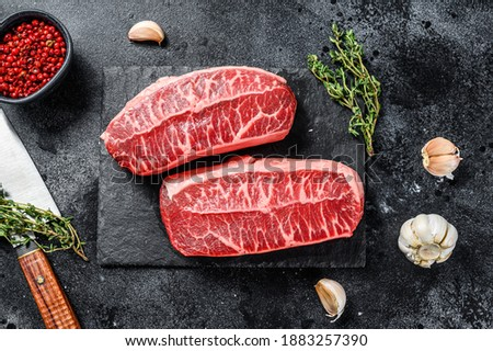 Raw organic meat Twagyu oyster top blade steak. Black background. Top view Royalty-Free Stock Photo #1883257390