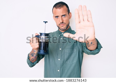 Young handsome man with tattoo holding french coffee maker with open hand doing stop sign with serious and confident expression, defense gesture