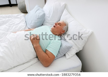 Mature man snoring while sleeping in bed. Apnea problem Royalty-Free Stock Photo #1883279356