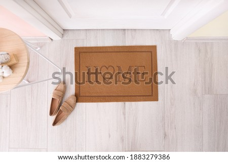 Door mat with shoes in hallway Royalty-Free Stock Photo #1883279386