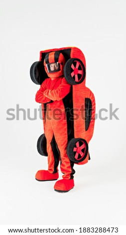 Portrait of a young cheerful man in a beautiful red suit of a racer in a helmet and a car behind his back on a white background. Animator in costumes. Entertainment for children