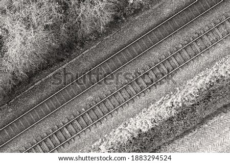 Black and white image of two railway tracks which consists of two parallel steel rails, anchored perpendicular to members called ties (sleepers) of concrete to maintain a consistent distance apart. Royalty-Free Stock Photo #1883294524