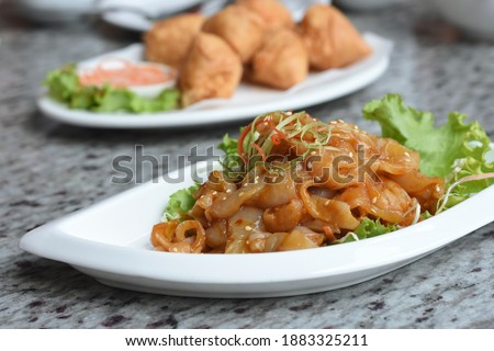 Front view of Jellyfish Sesame Oil with vegetables in white plate and blurred background of another dish, always served in Chinese Restaurant.