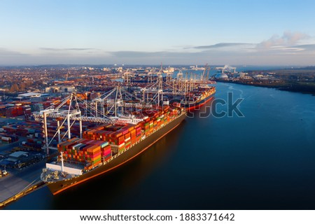 Aerial view of colorful containers on cargo ships at the port of Southampton, which is one of the Leading Port Terminal Operators in the UK. Containers on the dock too. Space for text. Royalty-Free Stock Photo #1883371642