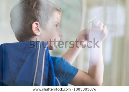 Small boy checking watermarks on the dollar bill. Children financial education concept image