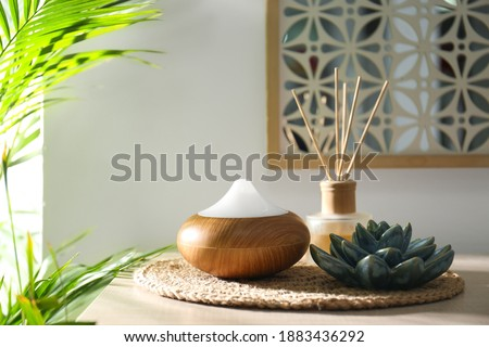 Aroma oil diffuser and reed air freshener on table in room Royalty-Free Stock Photo #1883436292