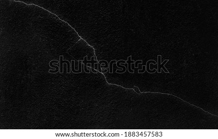 cracked on dark black wall texture background. aged black stucco cement wall that obsolated for a long time.