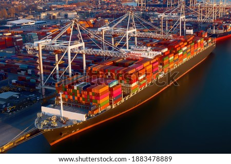 Aerial view of colorful containers on a cargo ship at the port of Southampton, which is one of the Leading Port Terminal Operators in the UK. With space for text. Royalty-Free Stock Photo #1883478889