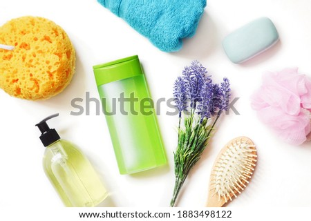 Green shampoo bottle, liquid soap, sponge, lavender flowers and wooden comb on a white. Bathroom stuff, natural organic bath products, toiletries set. Cosmetics for skin and hair care Royalty-Free Stock Photo #1883498122