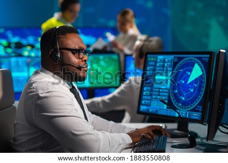 Workplace of the air traffic controllers in the control tower. Diverse team of aircraft control officers works using radar, computer navigation and digital maps. Aviation concept. Royalty-Free Stock Photo #1883550808