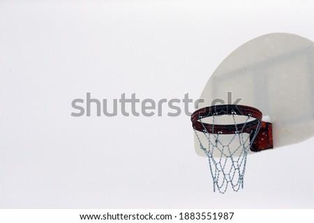 an outdoor basketball hoop in winter