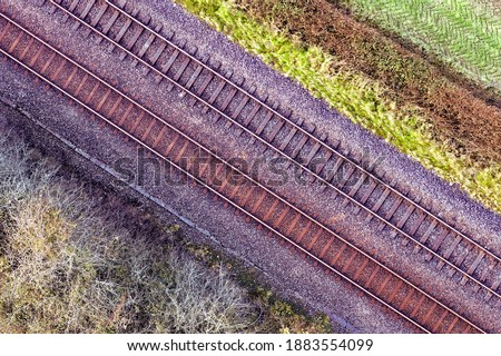 Romantic image of two railway tracks which consists of two parallel steel rails, anchored perpendicular to members called ties (sleepers) of concrete to maintain a consistent distance apart. Pattern. Royalty-Free Stock Photo #1883554099