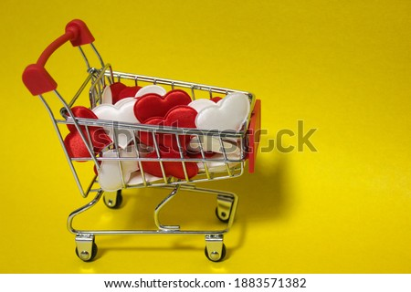 A small supermarket cart that is full of Valentine's Day hearts on a yellow background. Holiday of lovers, yellow, iron. Love, joy.