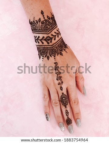 beautiful henna tattoo on the wrist and hand with pink background