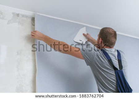 Wallpapering. A man glues gray vinyl wallpaper on a non-woven backing. Renovation of the room. Hang wallpaper. Home repairs. Royalty-Free Stock Photo #1883762704