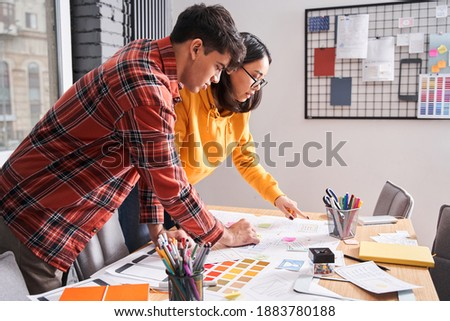 Sounds great. Two colleagues with cheerful eyes discussing something at the office while looking at the sketches at the table. Stock photo