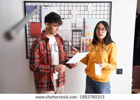 Developers of mobile application design are discussing new ideas while standing near the board with stickers and sketches. Stock photo