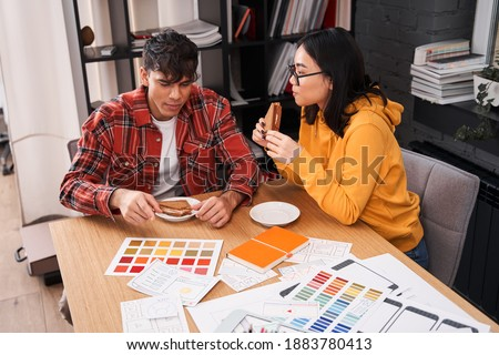 Developers of mobile application design sitting at the table, eating sandwiches and discussing new ideas at the lunch break. Stock photo