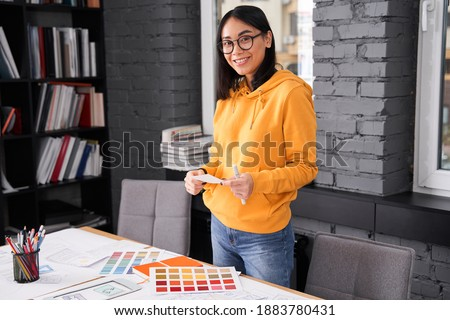 Waist up portrait of pleased girl wearing glasses standing at the table at the office while holding samples of colors. She is standing inside. Stock photo