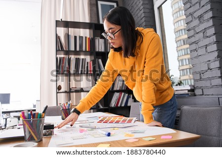 Young woman standing near desk with instruments, while working at the new project of the smartphone interface design. Stock photo
